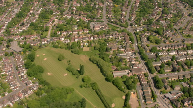 aerial view of a suburban housing estate in sunshine. 4k - uk stock videos & royalty-free footage