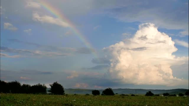 aerial view of a summer rainbow over green plains and meadows, time lapse - red cloud sky stock videos & royalty-free footage