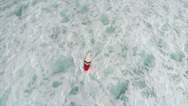 Aerial view of a surfboard in the whitewash waves of Hawaii. - Slow Motion