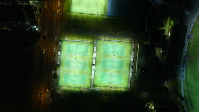 Aerial view of a tennis court at night.