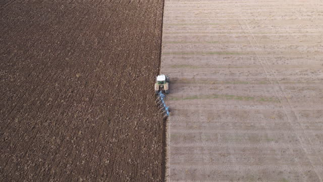 aerial view of a tractor plowing an agricultural field. tractor working at the end of the harvest season plowing the soil before sowing. agricultural occupation. - agricultural occupation stock videos & royalty-free footage