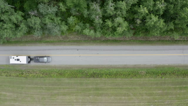 aerial view of a truck pulling a camper trailer on country road - camper van stock videos & royalty-free footage
