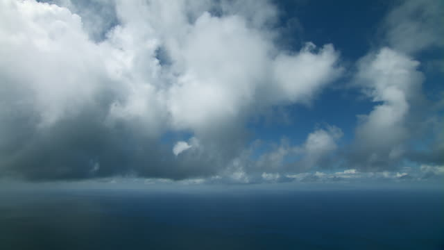 Aerial view of a vast ocean horizon and cumulus clouds.