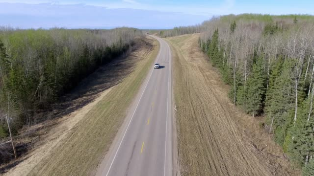 aerial view of a vehicle driving on a northern highway - alberta stock videos & royalty-free footage