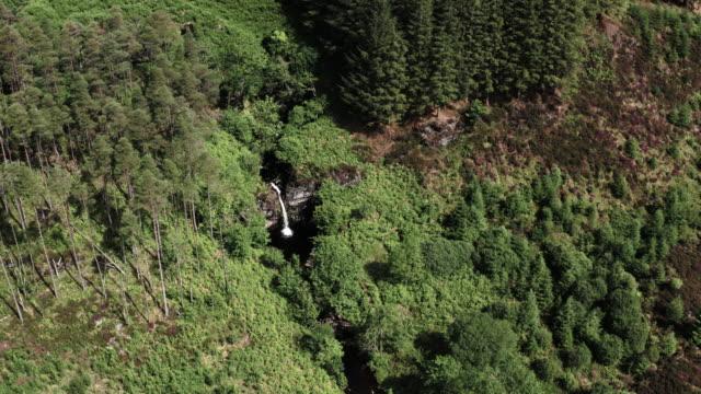 vidéos et rushes de vue aérienne d'une chute d'eau en cascade dans la petite rivière qui coule lentement dans un sud-ouest rural éloigné de l'ecosse - remote location