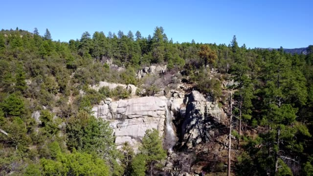 aerial view of a waterfall on the cliff of a mountainous pine tree forest in prescott arizona - prescott arizona stock videos & royalty-free footage