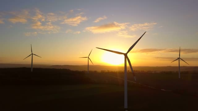 vidéos et rushes de aerial view of a wind farm in front of a sunrise, saargau near kirf, rhineland-palatinate, germany, europe - sunrise dawn
