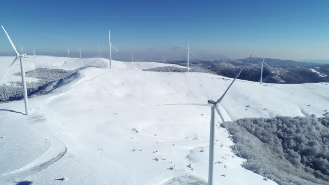 aerial view of a wind generators park in wintertime, on the top of the mountain, blue sky, daytime, snowcapped mountains, alternative energy - renewable energy stock videos & royalty-free footage