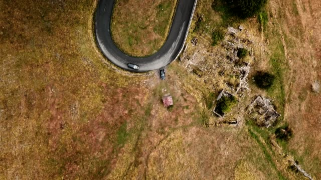 aerial view of a winding road with clouds - turning stock videos & royalty-free footage