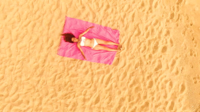 Aerial view of a woman lying down alone in an amazing and unspoiled beach in the spain coast