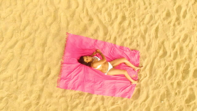 aerial view of a woman lying down alone in an amazing and unspoiled beach in the spain coast - bikinioberteil stock-videos und b-roll-filmmaterial
