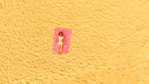 vídeos y material grabado en eventos de stock de aerial view of a woman lying down alone in an amazing and unspoiled beach in the spain coast - acostado
