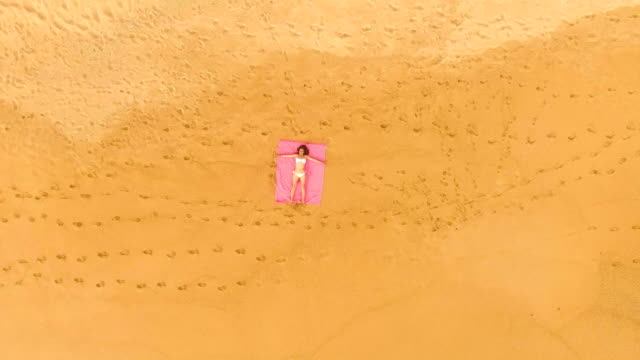 aerial view of a woman lying down alone in an amazing and unspoiled beach in the spain coast - zoom out stock videos & royalty-free footage