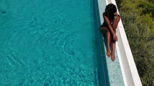 vídeos de stock, filmes e b-roll de vista aérea de uma mulher tomando banho de sol na piscina de beiral infinito - lago infinito