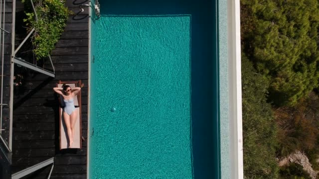 vídeos de stock e filmes b-roll de aerial view of a women sunbathing by the infinity pool - hotel