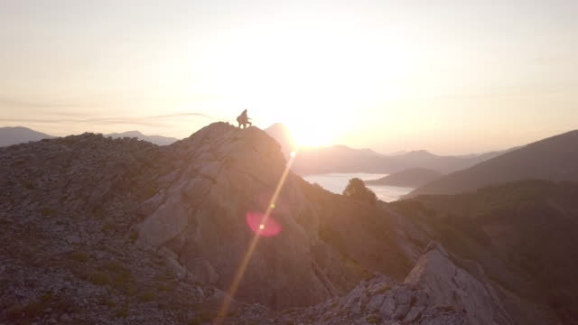 vidéos et rushes de aerial view of a young couple on the top of a mountain - admirer le paysage