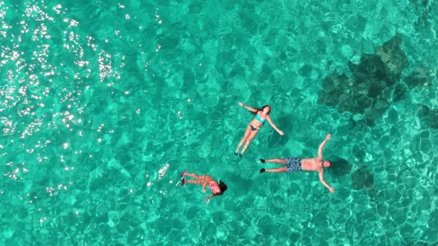 aerial view of a young family floating and swimming on beautiful beach at greek island - floating on water stock videos & royalty-free footage