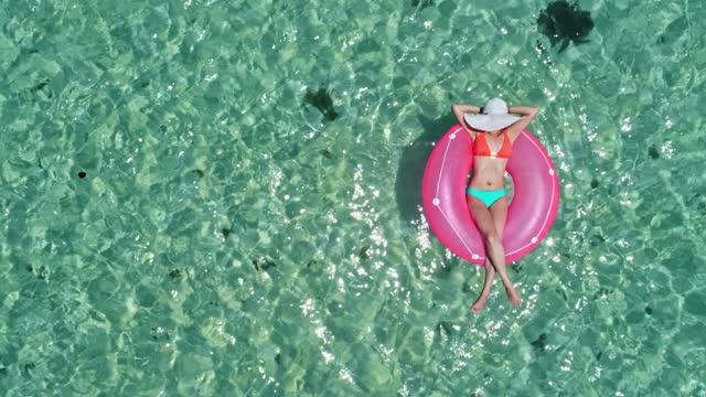 stockvideo's en b-roll-footage met luchtmening van een jonge vrouwen die op opblaasbare ring in een tropisch turkoois ongerept strand ontspannen. - badkleding