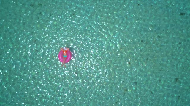 aerial view of a young women relaxing on inflatable ring in a tropical turquoise pristine beach. - rubber ring stock videos & royalty-free footage