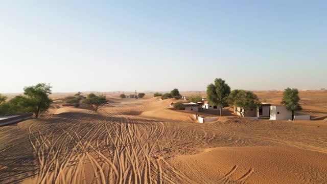 vídeos y material grabado en eventos de stock de vista aérea de casas abandonadas en el desierto de los eau cerca de dubái, traspasadas por dunas de arena - desert area