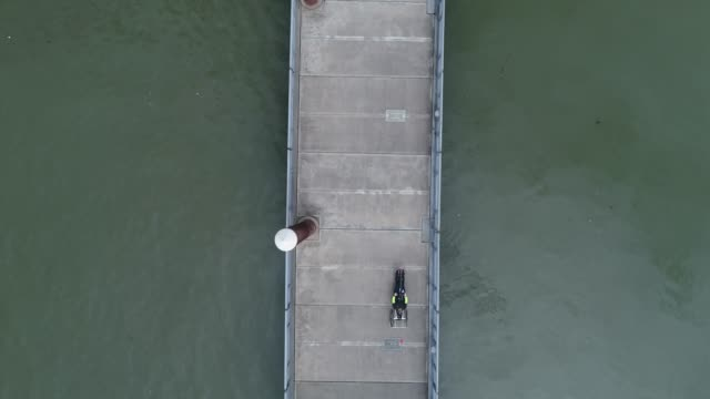 Aerial View of Adaptive Athlete Riding a Hand Powered Cycle on Floating Walkway