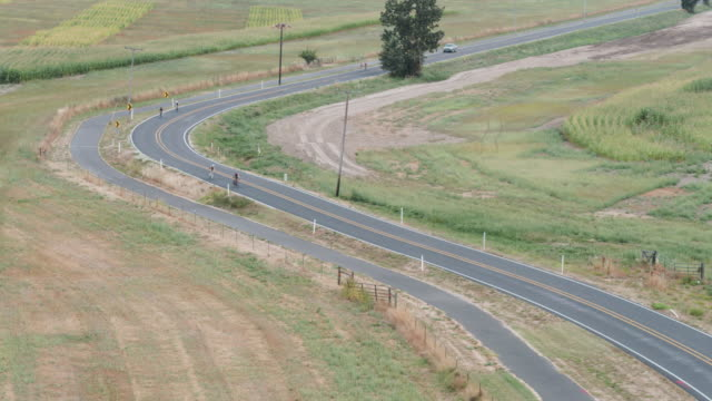 aerial view of adults riding road bikes along rural highway - 50 59 years stock videos & royalty-free footage