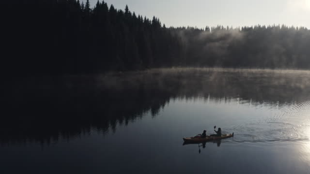 aerial view of adventure people kayaking in the mountains at sunrise, couple travelling with kayak. - standing water stock videos & royalty-free footage