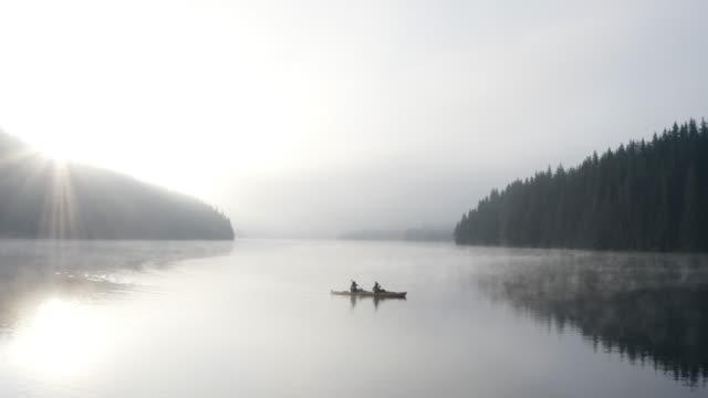 vídeos y material grabado en eventos de stock de vista aérea de la gente de aventura kayak en las montañas al amanecer, pareja viajando con kayak. - remar