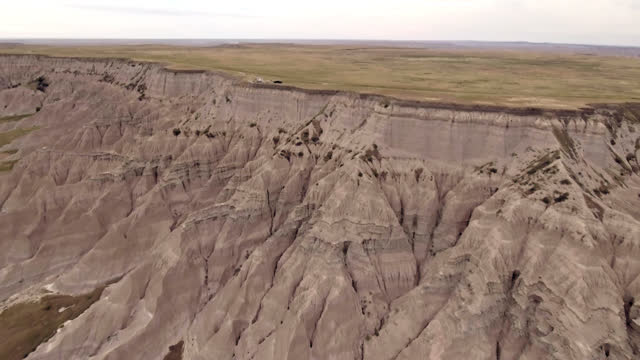 drone. aerial view of adventurous country road between hills and tree shrubs in badlands national park - badlands national park stock videos & royalty-free footage