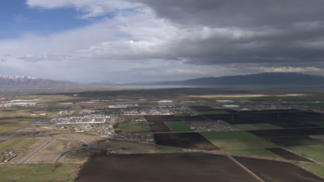 aerial view of agricultural fields on a cloudy day in springville, utah, united states of america. - springville utah stock-videos und b-roll-filmmaterial