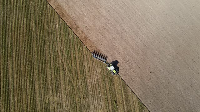 aerial view of agricultural tractor plowing a field - till stock videos & royalty-free footage