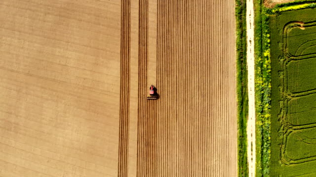aerial view of agricultural tractor plowing field - continuity stock videos & royalty-free footage
