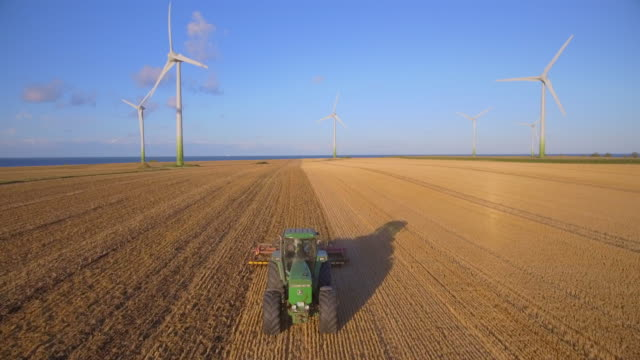 aerial view of agriculture cornfield with tractor plowing field and wind turbine on the island fehmarn - schleswig-holstein , germany - agricultural machinery stock videos & royalty-free footage