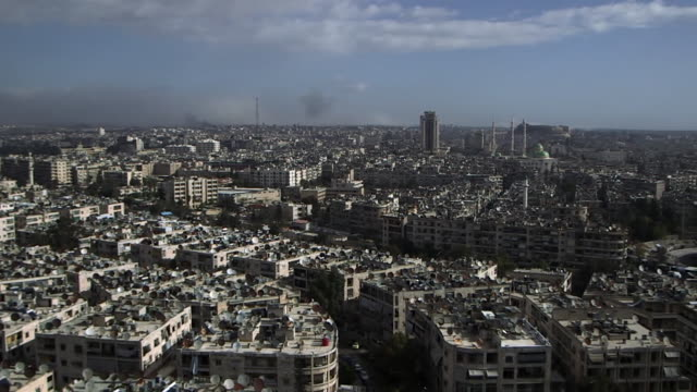 aerial view of aleppo showing explosions as syrian government forces do battle with rebels - syrien stock-videos und b-roll-filmmaterial