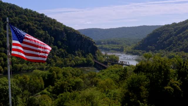 stockvideo's en b-roll-footage met luchtfoto van de amerikaanse vlag over historic harper's ferry, west virginia. - potomac rivier