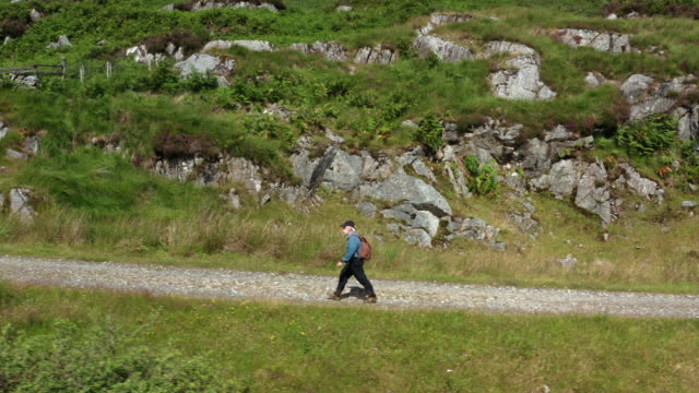aerial view of an active retired man walking on a dirt road in a remote part of south west scotland. - johnfscott stock videos & royalty-free footage