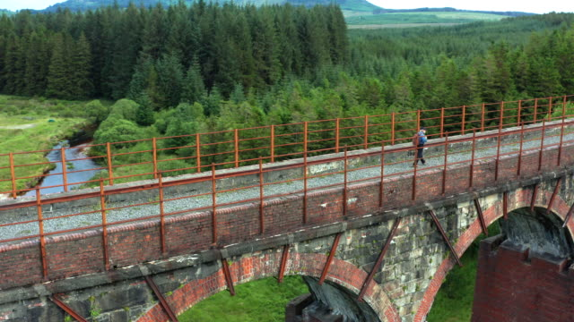 aerial view of an active retired man walking on a disused railway viaduct in a remote part of south west scotland. - johnfscott stock videos & royalty-free footage