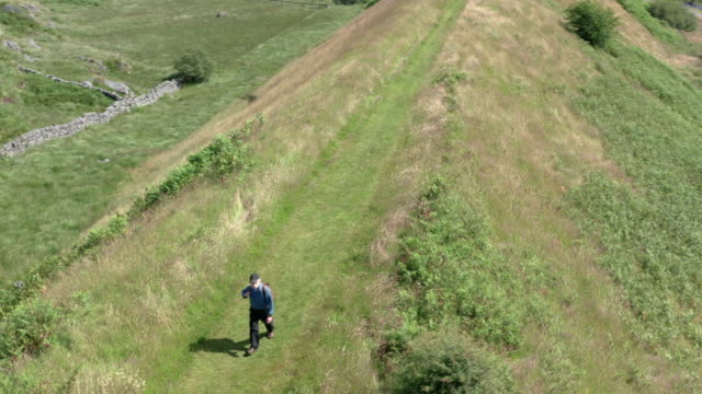 aerial view of an active retired man walking on a disused railway line in a remote part of south west scotland. - johnfscott stock videos & royalty-free footage