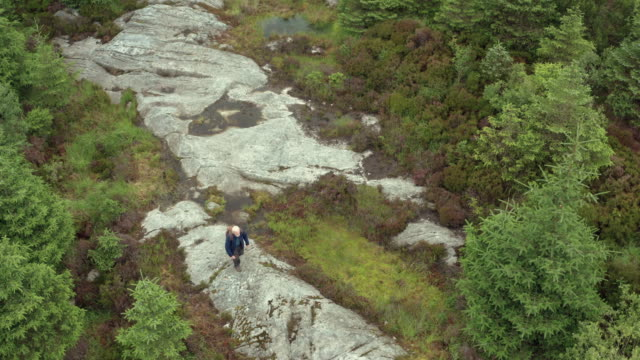 aerial view of an active senior man walking on a large granite outcrop in a remote part of rural south west scotland - johnfscott stock videos & royalty-free footage