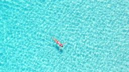Aerial view of an attractive woman floating in crystal clear sea