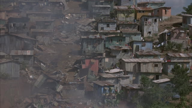 vídeos y material grabado en eventos de stock de aerial view of an impoverished village with a trail of debris as villagers group around yellow suv and blue jeep. - villa asentamiento humano