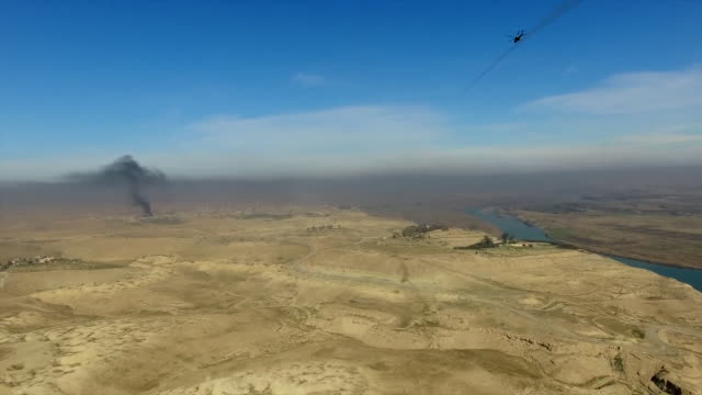 aerial view of an iraqi army helicopter firing at islamic state targets in mosul - kampfhubschrauber stock-videos und b-roll-filmmaterial