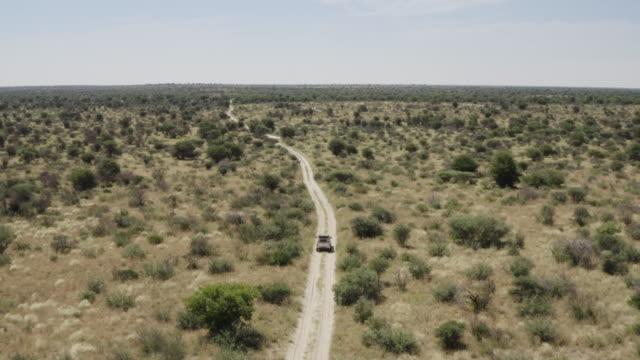 vídeos de stock e filmes b-roll de aerial view of an off-road vehicle driving through the kalahari desert - savana