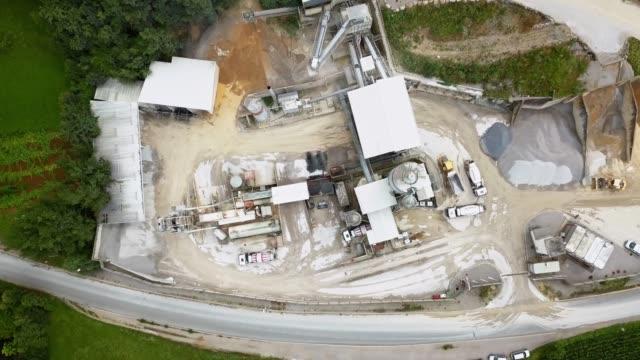 stockvideo's en b-roll-footage met luchtmening van een open mijn met mijnbouwinstallatie die door bos wordt omringd - mijnindustrie