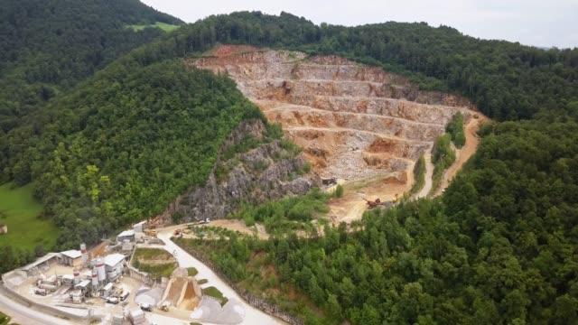 森林に囲まれた鉱山工場を持つ露天掘り鉱山の空中写真 - 堆積岩点の映像素材/bロール
