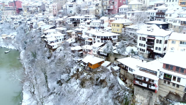 Aerial view of an urban landscape in wintertime with white snow-covered roofs and winding river bed