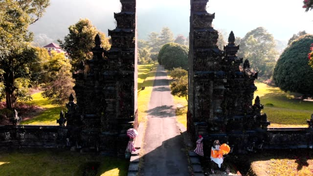 aerial view of ancient gate of balinese in green field and mountain background - temple building stock videos & royalty-free footage