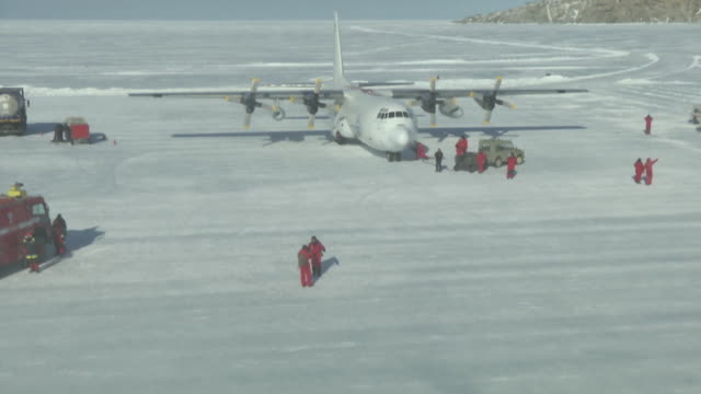 aerial view of antarctic expedition vehicles unloading and fueling plane - antarctica research stock videos & royalty-free footage