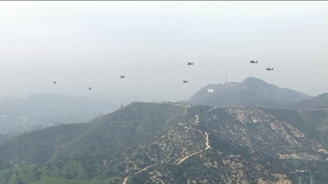 ktla aerial view of apache and blackhawk helicopters flying over hollywood sign - アパッチヘリコプター点の映像素材/bロール