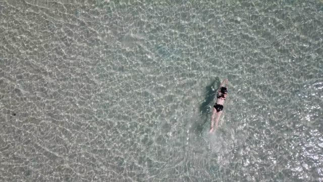 aerial view of asian woman swimming and floating on crystal clear water sea - swimming stock videos & royalty-free footage